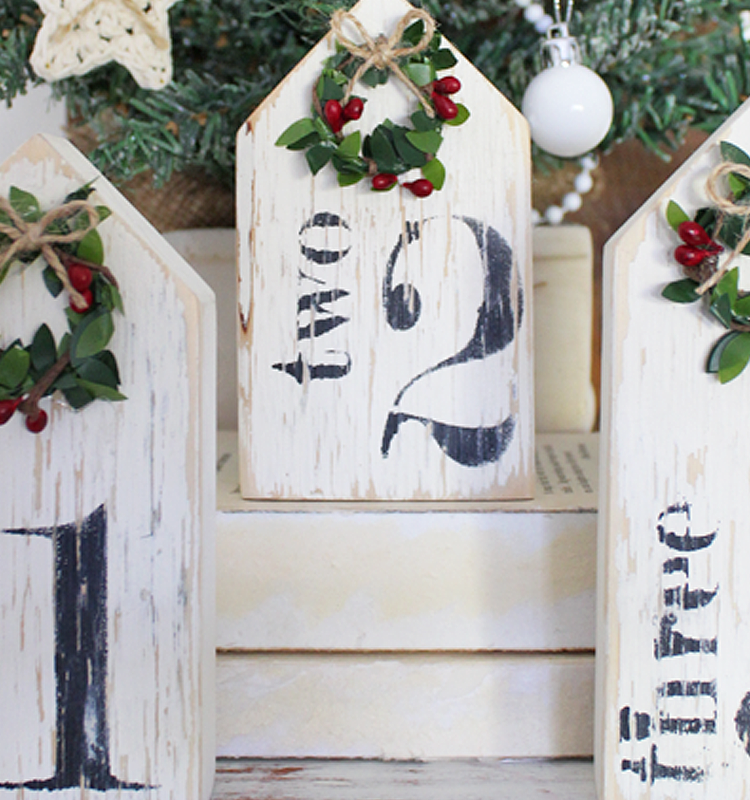 A fun gift idea or a little project for yourself with this DIY Farmhouse Numbered Christmas Houses Kit. Comes complete with pre cut houses, Fusion Mineral Paint - Coal Black and Raw Silk, Cling On! Paint Brush, 3 Number Stencils and 3 Handmade Wreaths | www.raggedy-bits.com | #raggedybits #DIY #Christmas #Kit #houses #stencils #clingon #fusionmineralpaint #fusionmineralpaint #coalblack #rawsilk #handmadewreaths